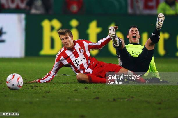 Holger Badstuber of Muenchen is challenged by Tolgay Arslan of Aachen during the DFB Cup quarter final match between Alemannia Aachen and Bayern...