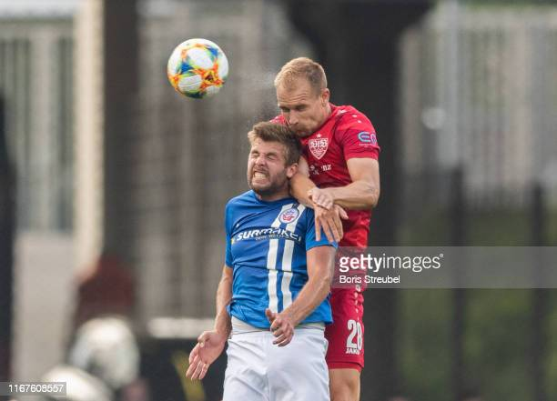 Holger Badstuber of VfB Stuttgart jumps for a header with Marco Koenigs of Hansa Rostock during the DFB Cup first round match between Hansa Rostock...