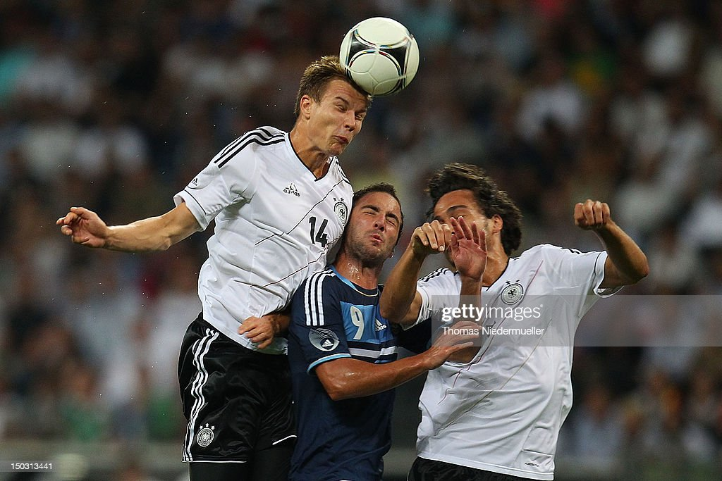 Holger Bartstuber (L) of Germany jumps for a headder with Gonzalo Higuain (C) of Argentina and Mats Hummels (R) of Germany during the international friendly match between Germany and Argentina and Commerzbank-Arena on August 15, 2012 in Frankfurt am Main, Germany.