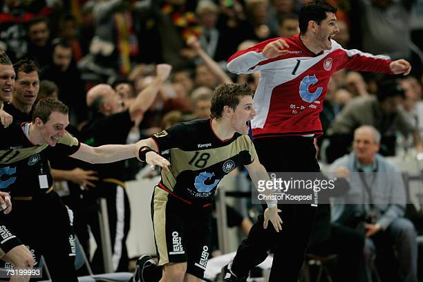 Holger Glandorf, Michael Kraus and Henning Fritz celebrate their victory over Poland after the IHF World Championship final between Germany and...