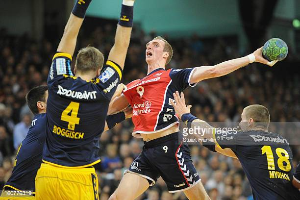 Holger Glandorf of Flensburg challenges for the ball with earko Šešum and Bjarte Myrhol of RheinNeckar during the DHB cup game between SG Flensburg...