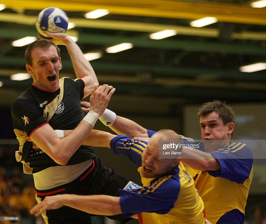 Holger Glandorf of Germany in action with two players of Sweden during the Men's Handball European Championship main round Group II match between Hungary and Iceland at Trondheim Spektrum on January 23, 2008 in Trondheim, Norway.