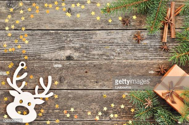 holiday card for the new year is 2019 in warm, trendy colors. christmas composition of spruce branches, gift, cinnamon, anise and confetti stars on rustic wooden background. flat plan, top view - hello december stock pictures, royalty-free photos & images