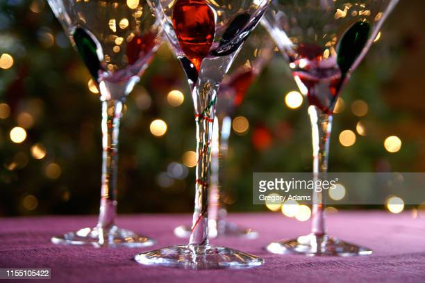 holiday celebration - crystal glasses in front of an out of focus christmas tree - nieuwjaarsreceptie stockfoto's en -beelden