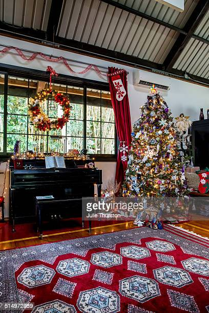 Holiday Christmas tree next to piano and red rug