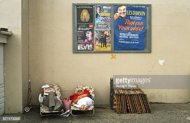 A holiday couple sleep on portable beds in a particularly shabby corner of Bournemouth a seaside resort in southern England Above them are posters...