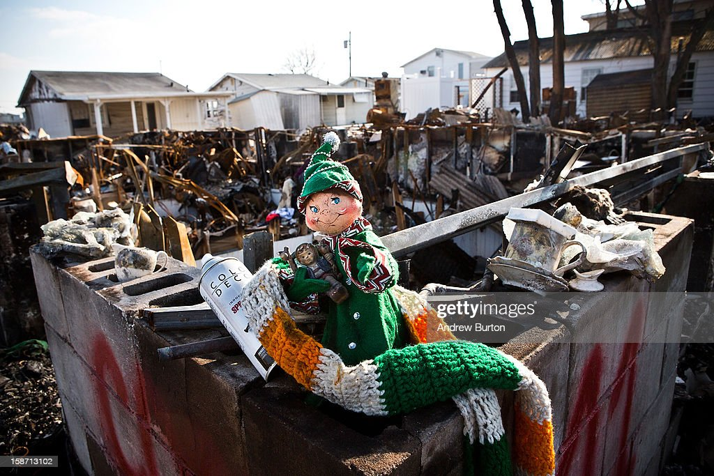 A holiday doll rests amongst the remains of burned houses in the Breezy Point neighborhood of the Borough of Queens on December 25, 2012 in New York City.