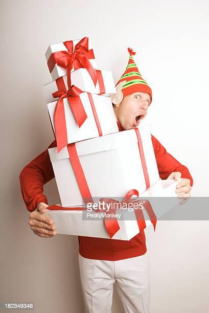 Urlaub Elf Mann Holding Stack von Geschenken überrascht suchen