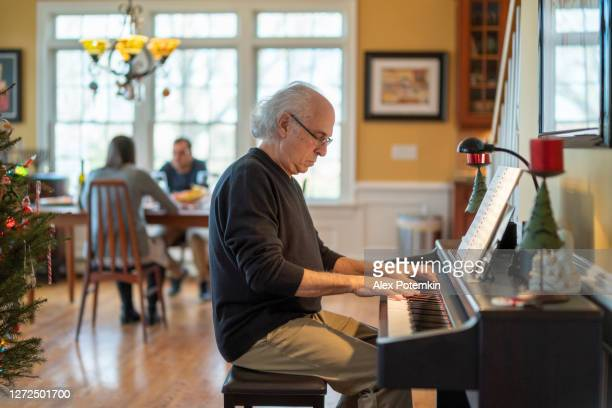 holiday family reunion. the senior 72-years-old silver-hair man, the musician, playing piano for his family who is dinning in the backdrop in the bright spacious living room decorated for christmas. - 25 29 years stock pictures, royalty-free photos & images