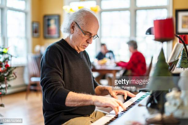 holiday family reunion. the senior 72-years-old silver-hair man, the musician, playing piano for his family who is dinning in the backdrop in the bright spacious living room decorated for christmas. - 65 69 years stock pictures, royalty-free photos & images