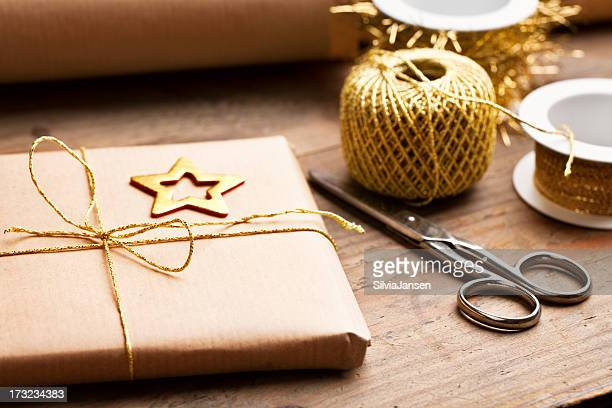 Holiday gift wrapped in eco-paper with gold ribbon