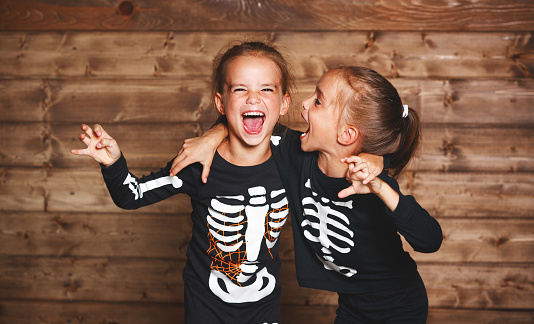 holiday halloween. funny funny sisters twins children in carnival costumes skeleton  on wooden 840451126