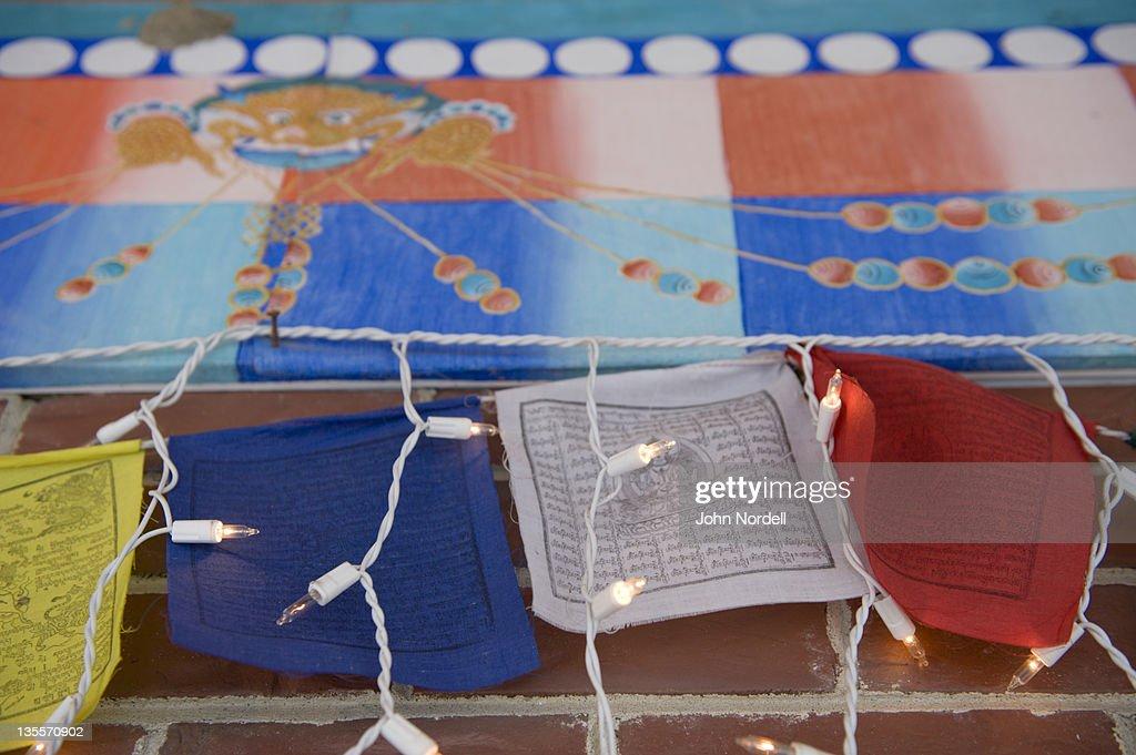 Holiday Lights Draped Over Tibetan Prayer Flags With Tibetan Symbol