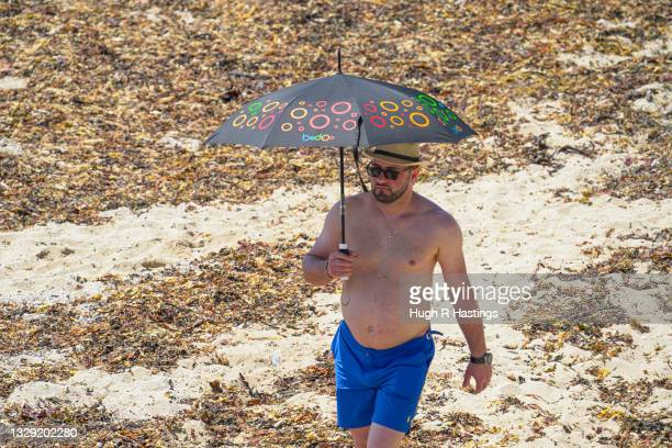 Holiday maker takes shelter from the sun on Gyllyngvase Beach on July 17, 2021 in Falmouth, United Kingdom. A heat related health warning has been...