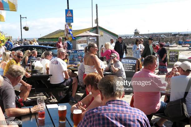 Holiday makers and locals sit outside The Sloop in founded in 1312 St Ives during the 2019 September Summer Festival St Ives has become renowned for...