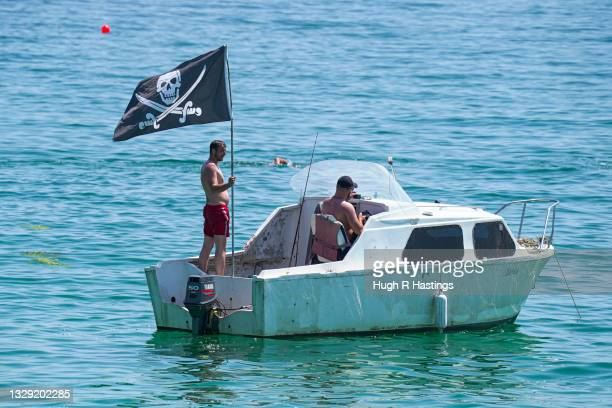 Holiday makers float in a boat with a pirate flag near Gyllyngvase Beach on July 17, 2021 in Falmouth, United Kingdom. A heat related health warning...