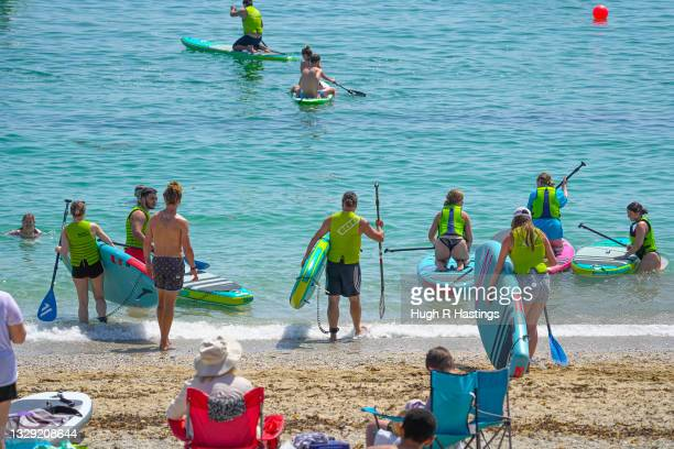 Holiday makers gather to enjoy the sun on Gyllyngvase Beach on July 17, 2021 in Falmouth, United Kingdom. A heat related health warning has been...