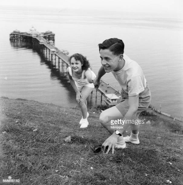 Holiday makers in Llandudno Conwy County Borough A young couple climbing up a hilly bank with the pier in the background 22nd August 1949