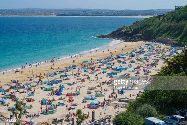 Holiday makers on Porthminster Beach on August 9, 2020 in St Ives, Cornwall, England. The RNLI has called on beachgoers in the south west of England...