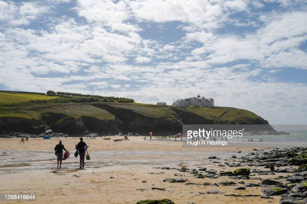 Holiday makers on the beach during the August tourist season in Cornwall on August 23rd at Poldhu Cove, The Lizard Cornwall, United Kingdom. The...