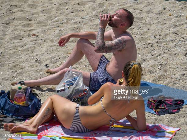 Holiday makers refresh themselves with a drink on Gyllyngvase Beach on July 17, 2021 in Falmouth, United Kingdom. A heat related health warning has...