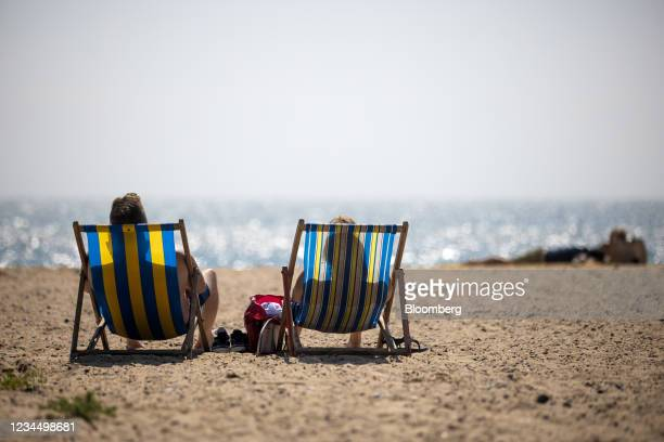 Holiday makers sit in deckchairs on the beach in Great Yarmouth, U.K., on Wednesday, Aug. 4, 2021. The second pandemic summer has offered a lifeline...