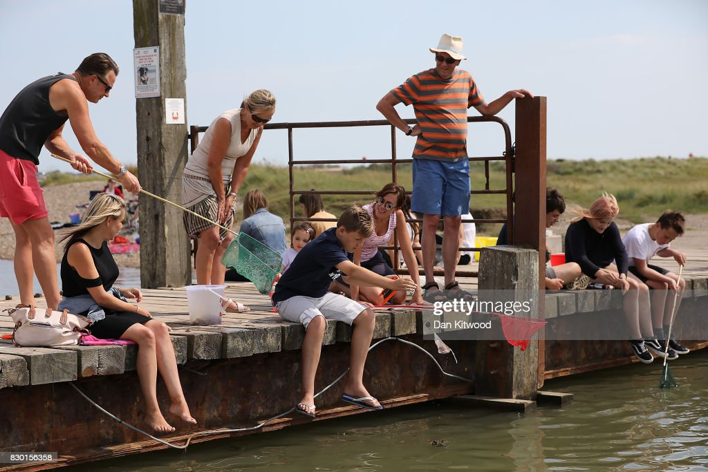 Holiday makers sit on a wooden bridge while fishing for crabs on August 11, 2017 in Walberswick, England. Much of the country is expected to enjoy a sunny spell over the weekend after a period of unseasonably wet weather.