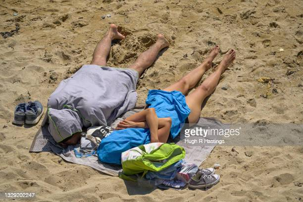 Holiday makers take shelter from the sun on Gyllyngvase Beach on July 17, 2021 in Falmouth, United Kingdom. A heat related health warning has been...