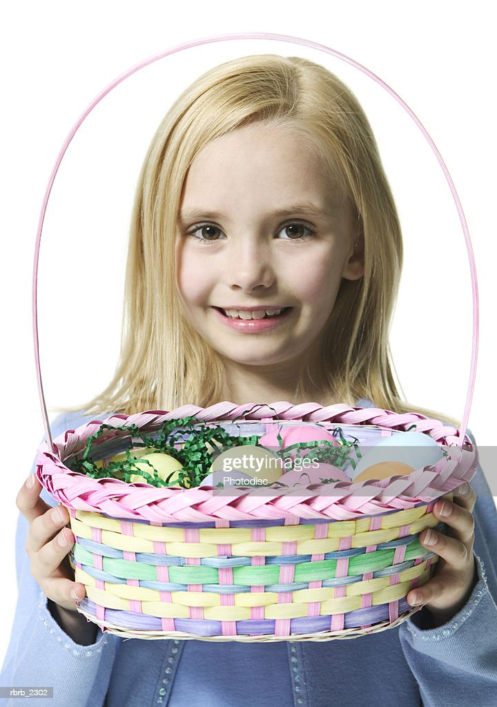 holiday portrait of a blonde female child as she holds up an easter basket : Foto de stock