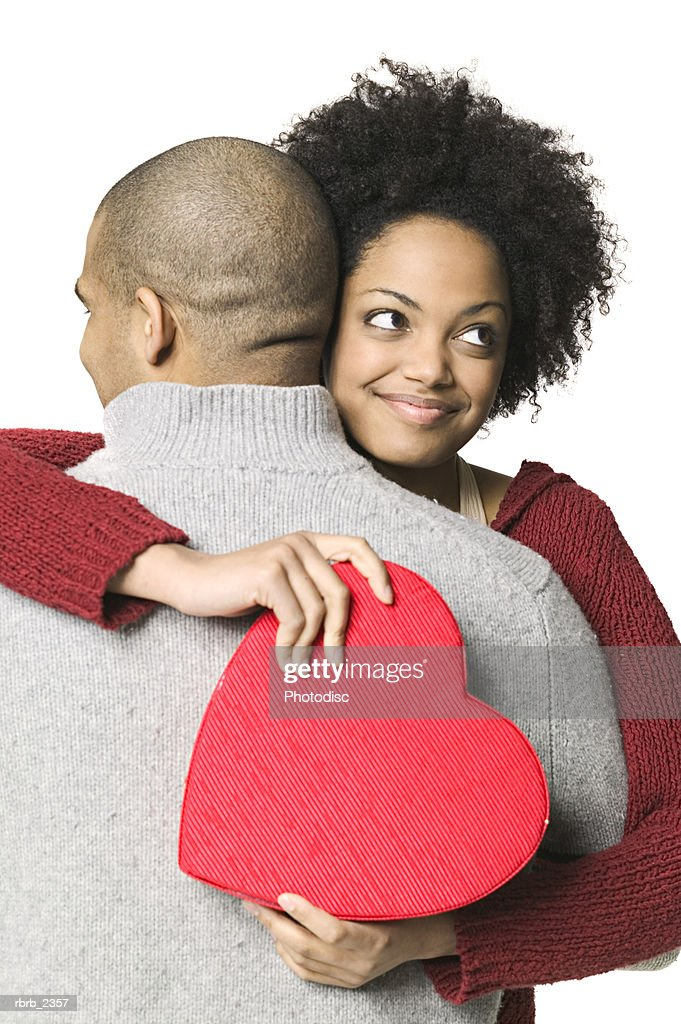 holiday portrait of a young adult woman as she holds a heart shaped box and hugs her boyfriend : Foto de stock