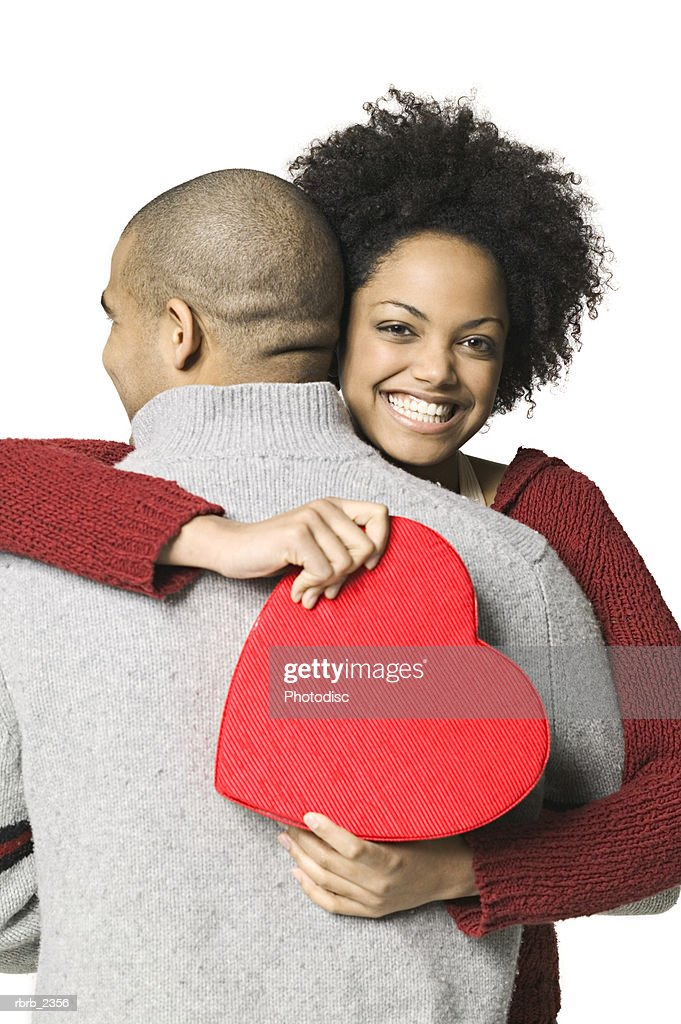 holiday portrait of a young adult woman as she holds a valentine box and hugs her boyfriend : Foto de stock