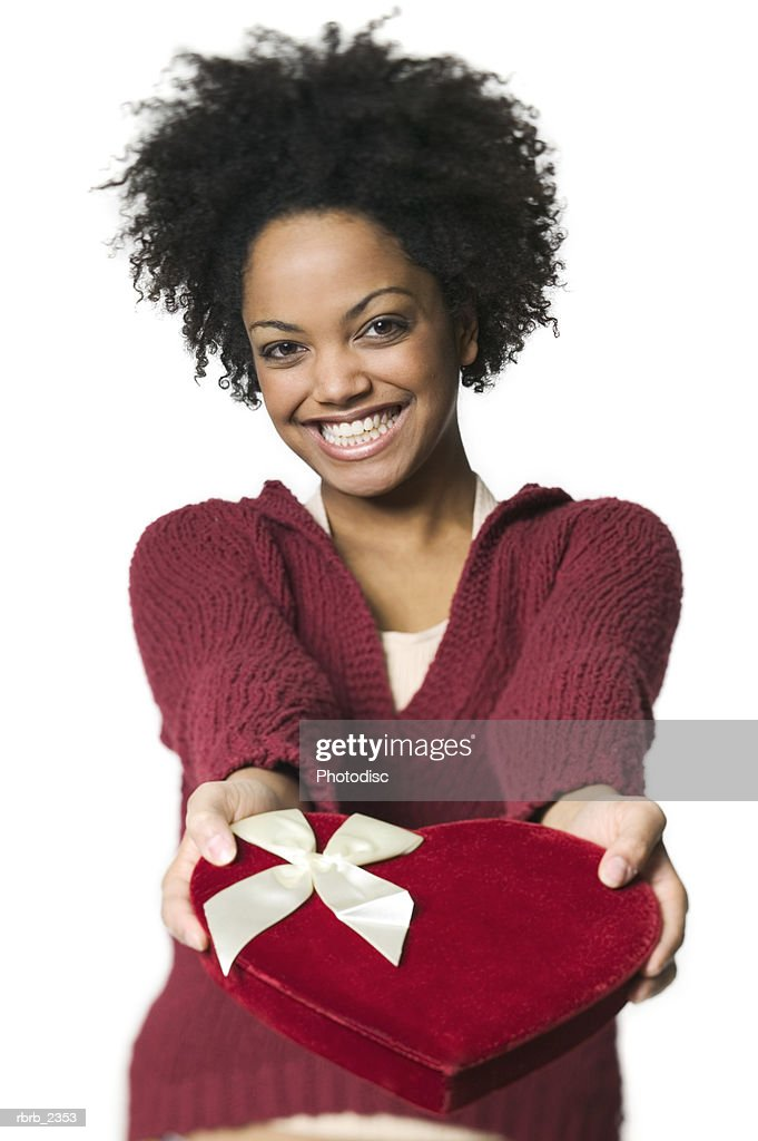 holiday portrait of a young adult woman as she holds out a heart shaped valentine box : Stock Photo