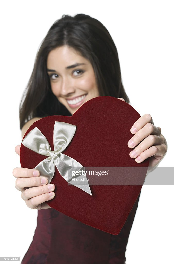 holiday portrait of an attractive young adult woman as she holds out a heart shaped box : Foto de stock