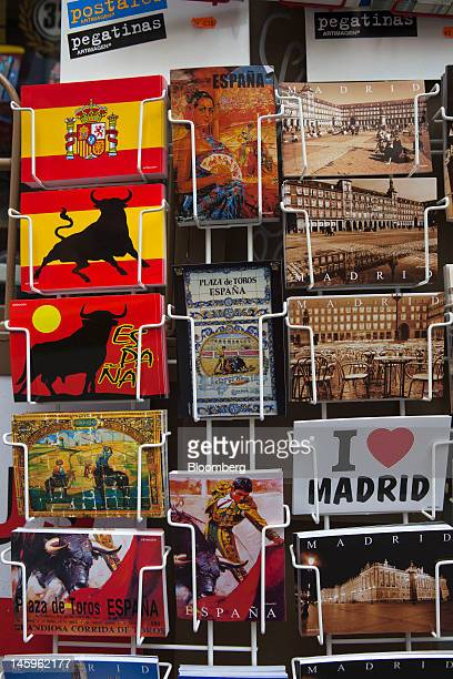 Holiday postcards stand for sale on a rack outside a souvenir store for tourists in Madrid Spain on Friday June 8 2012 Spain is poised to become the...