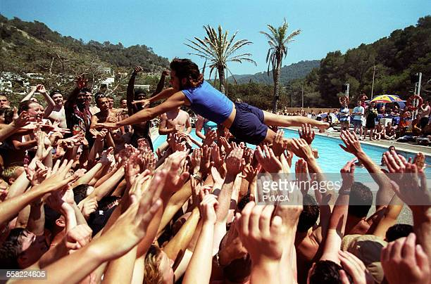 A holiday rep diving into a crowd of people at a pool party Club 1830 Ibiza 2001