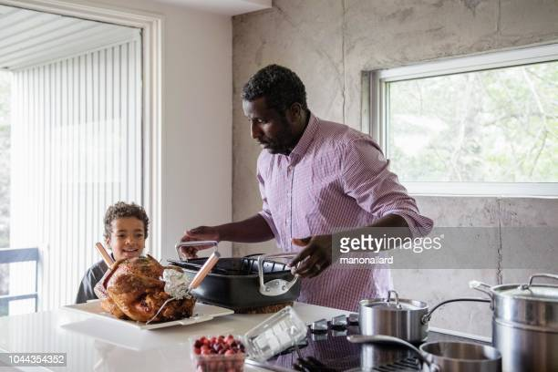 holiday season family and friends multi-ethnic during thanksgiving dinner - black family dinner stock photos and pictures