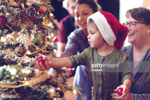 holiday season : family decorating the christmas tree - tradition stock pictures, royalty-free photos & images