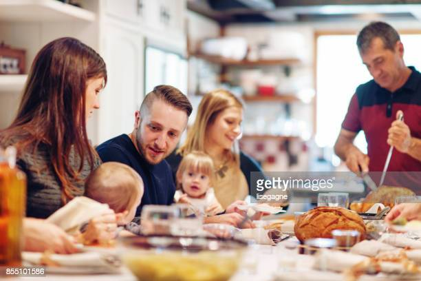 holiday season : family having thanksgiving dinner - large family stock pictures, royalty-free photos & images