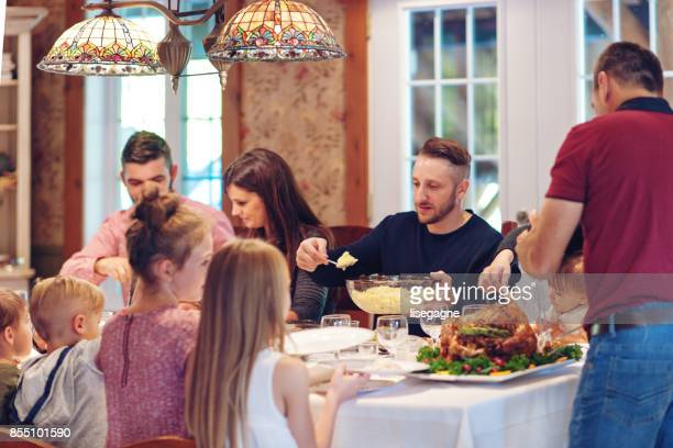 holiday season : family having thanksgiving dinner - canadian thanksgiving stock pictures, royalty-free photos & images