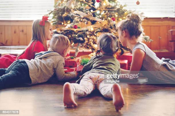 holiday season : kids around the christmas tree - christmas gifts stock photos and pictures