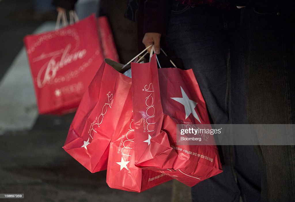 Holiday shoppers carry Macy's Inc. shopping bags in New York, U.S., on Sunday, Dec. 23, 2012. Holiday shoppers descended on U.S. stores this weekend in a last-minute dash to buy gifts amid concerns about the nation's economy and the impasse in Washington over taxes and spending. Photographer: Victor J. Blue/Bloomberg via Getty Images