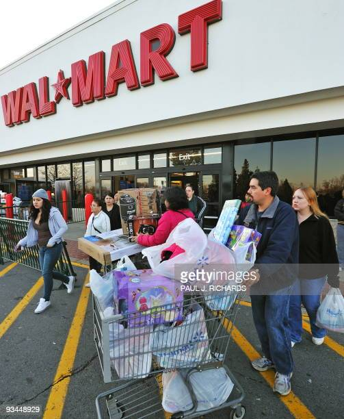 Holiday shoppers leave the WalMart store in Fairfax Virginia early November 27 2009 after taking advantage of the Black Friday discount sales The...