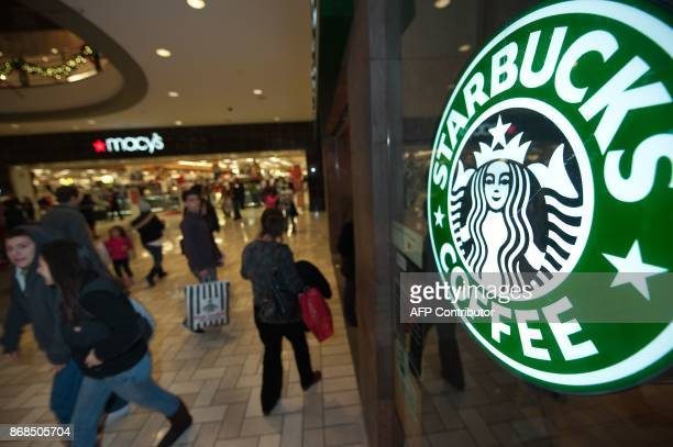 Holiday shoppers walk past a Starbucks Coffee shop December 23 2009 at Tyson's Corner mall in McLean Virginia US retailers are scrambling to stave...