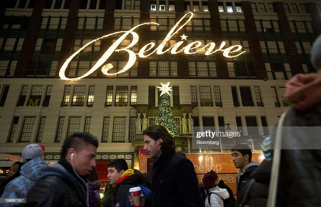 Holiday shoppers walk under a sign that reads 'Believe' on the facade of Macy's Inc. department store in New York, U.S., on Sunday, Dec. 23, 2012. Holiday shoppers descended on U.S. stores this weekend in a last-minute dash to buy gifts amid concerns about the nation's economy and the impasse in Washington over taxes and spending. Photographer: Victor J. Blue/Bloomberg via Getty Images
