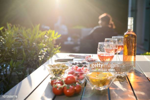 holiday summer brunch party table outdoor in house backyard with appetizer, glass of rose wine, fresh drink and organic vegetables. - olive fruit stock pictures, royalty-free photos & images