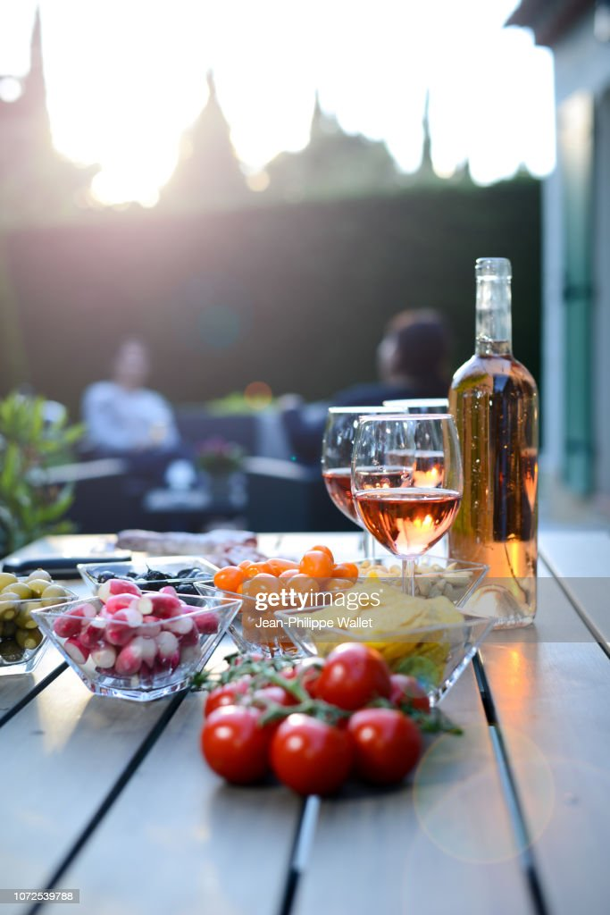 Holiday summer brunch party table outdoor in house backyard with appetizer, glass of rose wine, fresh drink and organic vegetables. : Foto de stock