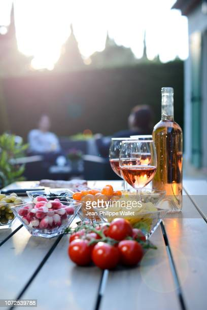 Holiday summer brunch party table outdoor in house backyard with appetizer, glass of rose wine, fresh drink and organic vegetables.