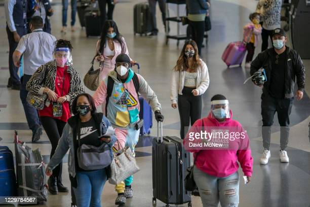 Holiday travelers pass through Los Angeles international Airport on Thanksgiving eve as the COVID-19 spike worsens and stay-at-home restrictions are...