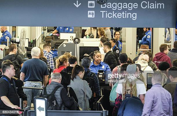 Holiday travelers wait in line to go through the security checkpoint at the Los Angeles International Airport California on December 22 2016 / AFP /...