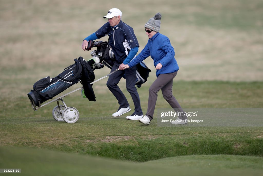 Holidaymaker Jeanette Siehenthiler (right) on the 18th hole with her caddie at Muirfield Golf Club, following the announcement that women will be admitted as members after a ballot was held by The Honourable Company of Edinburgh Golfers.